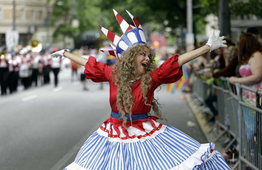 A woman dances past parade watchers at the 41st annual Pride Parade Sunday, June 28, 2015, in Seattle. Large turnouts were expected for gay pride parades across the U.S. following the landmark Supreme Court ruling that said gay couples can marry anywhere in the country. (AP Photo/Elaine Thompson)
