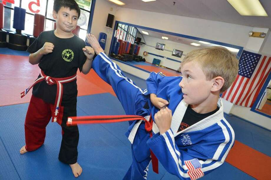 Hour Photo / Alex von Kleydorff 10 year olds Thomas Bovi and Henry Murrales show their Red Belt moves during a class at the Norwalk TaekwondoAcademy