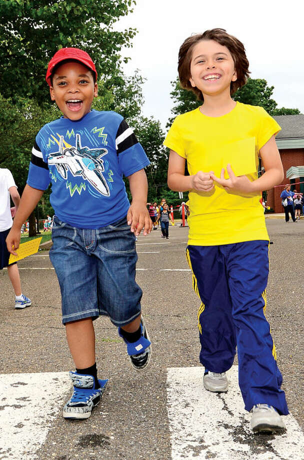 Hour photo / Erik Trautmann Fox Run Elementary School students Bazan Devellon and Leo Gonzales walk together as the school holds their annual fundraising walkathon where students gather sponsors to help reach the fundraising goal of $10,000.00. The fundraiser will benefit a plan to buy air conditioners for all the classrooms and new playground equipment.