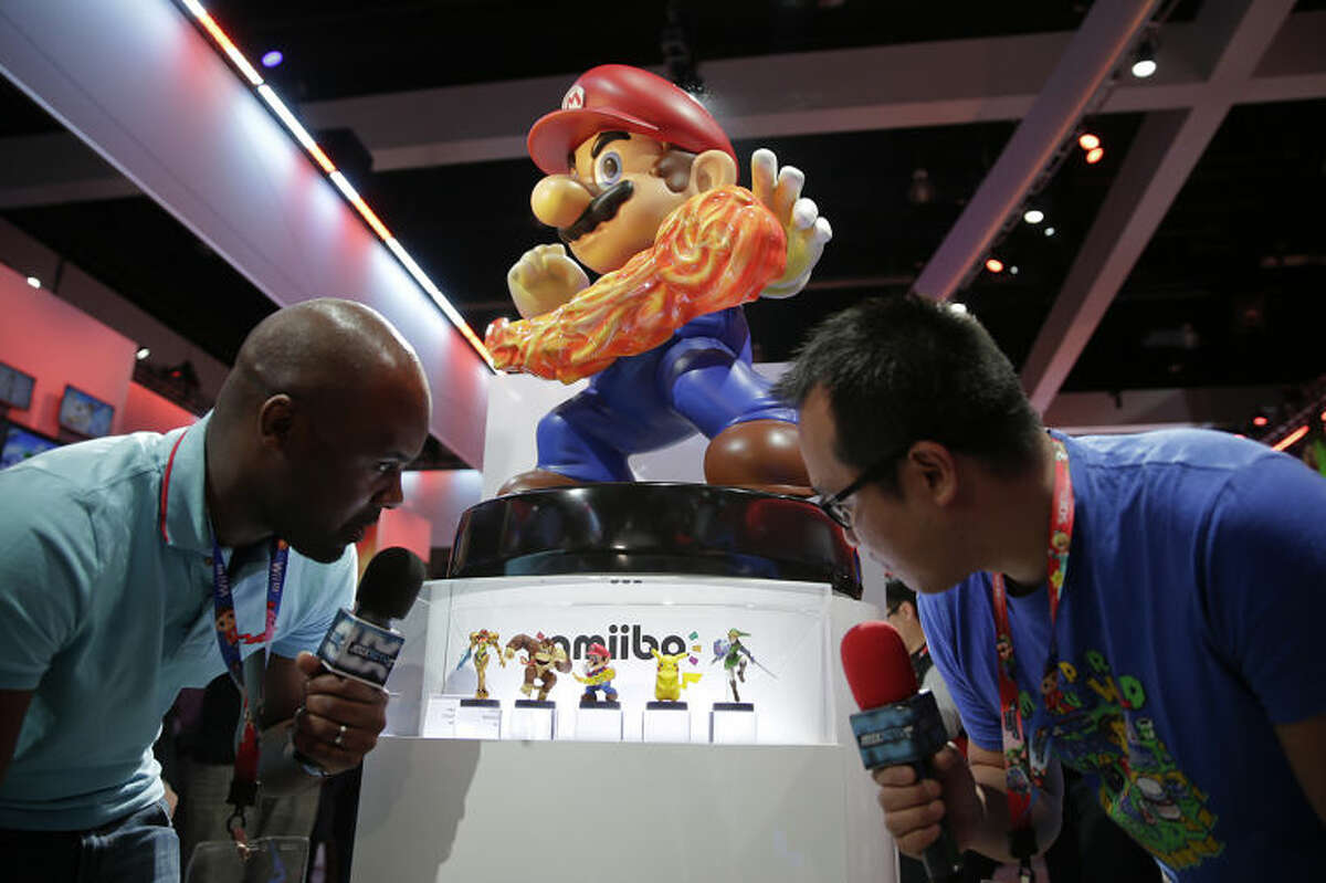 French television reporters look at Amiibo characters for Wii U at the Nintendo booth during the Electronic Entertainment Expo on Tuesday, June 10, 2014, in Los Angeles. (AP Photo/Jae C. Hong)