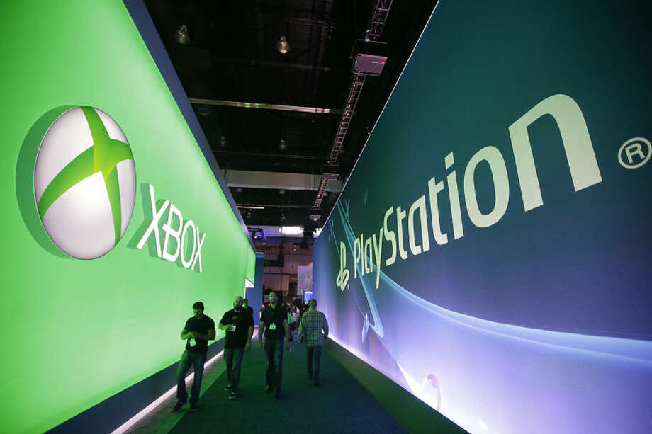 People walk along the aisle between the Microsoft booth and the Sony booth at the Electronic Entertainment Expo on Tuesday, June 10, 2014, in Los Angeles. (AP Photo/Jae C. Hong)