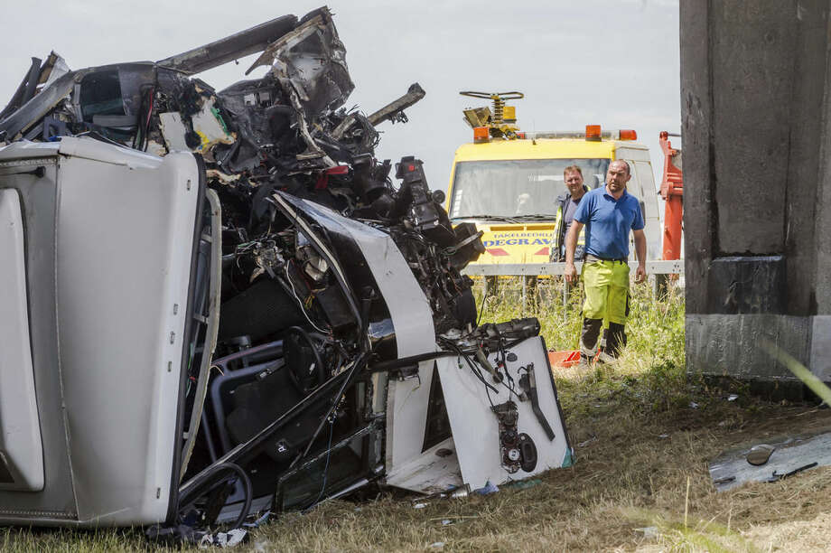 Safety workers attend to a bus which crashed on a motorway in Middlekerke, Belgium on Sunday, June 28, 2015. The bus, carrying British schoolchildren went off the highway and overturned near the Belgian coast on Sunday, injuring the driver and some of the children and killing one of the adults accompanying them. (AP Photo/Geert Vanden Wijngaert)