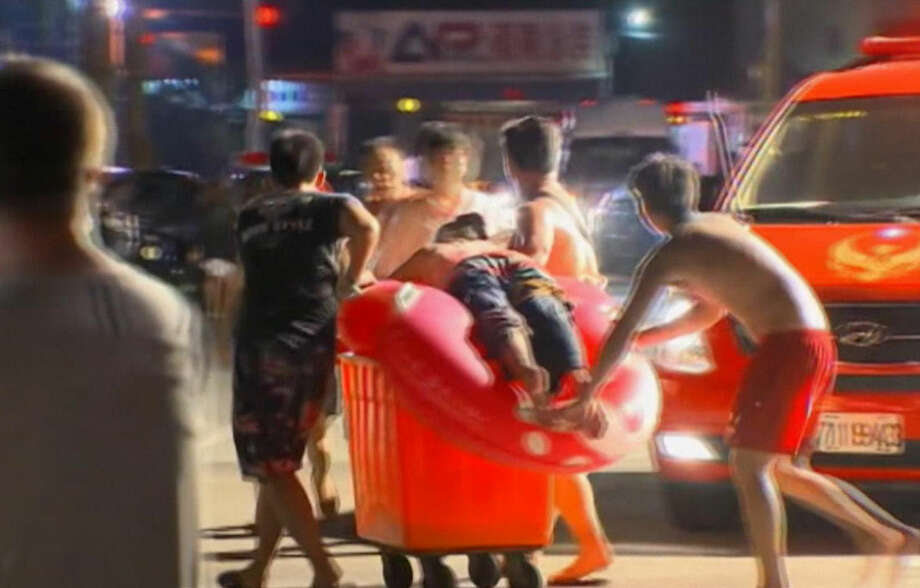 In this screen grab taken from ETTV, an injured concert spectator is treated after an accidental explosion during a music concert at the Formosa Water Park in New Taipei City, Taiwan, Saturday, June 27, 2015. The New Taipei City fire department says 200 people were injured in an accidental explosion of colored theatrical powder Saturday night near a performance stage where about 1,000 people were gathered for party. (ETTV via AP)