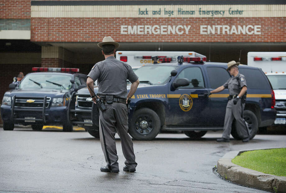 Law enforcement officers stands outside Alice Hyde Medical Center in Malone, N.Y., on Sunday, June 28, 2015, where David Sweat was taken after being shot and captured. Sweat's capture came two days after his fellow escapee, Richard Matt, was killed in a confrontation with law enforcement while holding a shotgun. Sweat was unarmed when he was shot twice by a state police sergeant as the fugitive ran for a tree line. (Jason Hunter/Watertown Daily Times via AP)