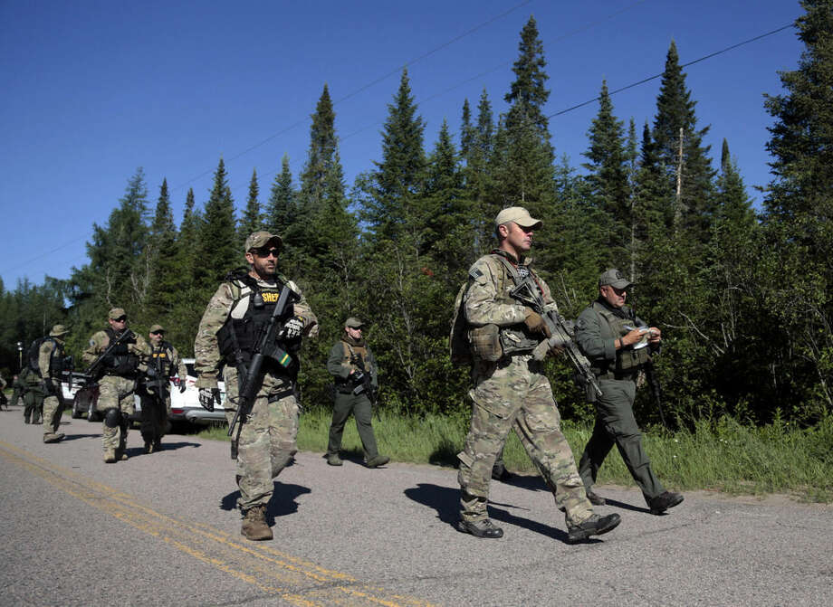 FILE - In this Wednesday, June 24, 2015, file photo, Law enforcement officers walk along a road before going into the woods near Mountain View, N.Y., as the search continued for Richard Matt and David Sweat, two escaped prisoners from Clinton Correctional Facility. Matt was shot and killed Friday, June 26, and Sweat was shot and captured Sunday. (AP Photo/Mike Groll, File)