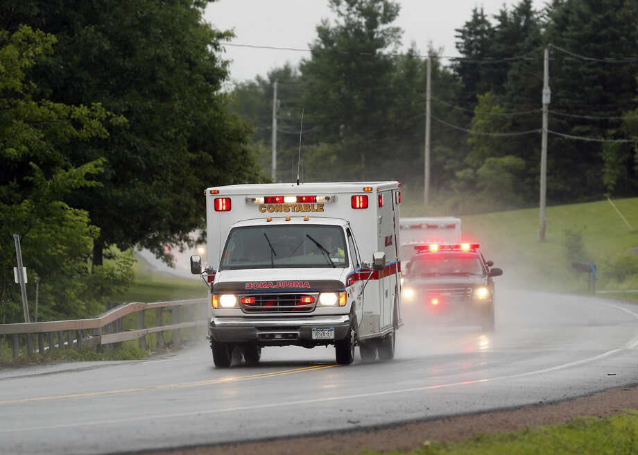 Police escort ambulances from an area where law enforcement officers were searching for convicted murderer David Sweat, one of two convicted murderers who broke out of a maximum-security prison near the Canadian border, Sunday, June 28, 2015, in Constable, N.Y. The other inmate, Richard Matt, was shot three times in the head when he was confronted by authorities on Friday. (AP Photo/Mike Groll)