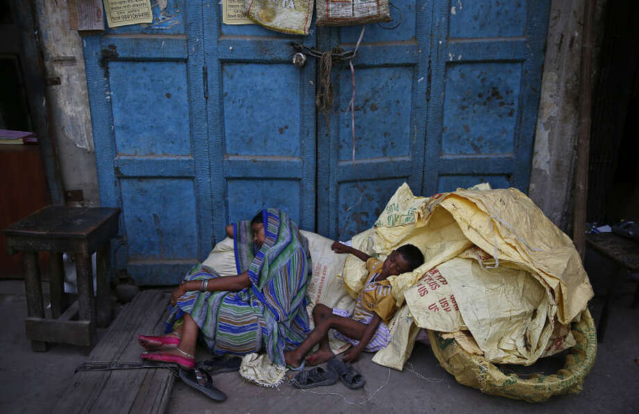 A mother and her child sleep on a pavement in the shade of a building on a hot summer afternoon in New Delhi, India, Wednesday, June 11, 2014. Heat wave conditions continued unabated in the northern plains of the country with temperatures soaring past 45 degrees Celsius (113 Fahrenheit). (AP Photo/Saurabh Das)