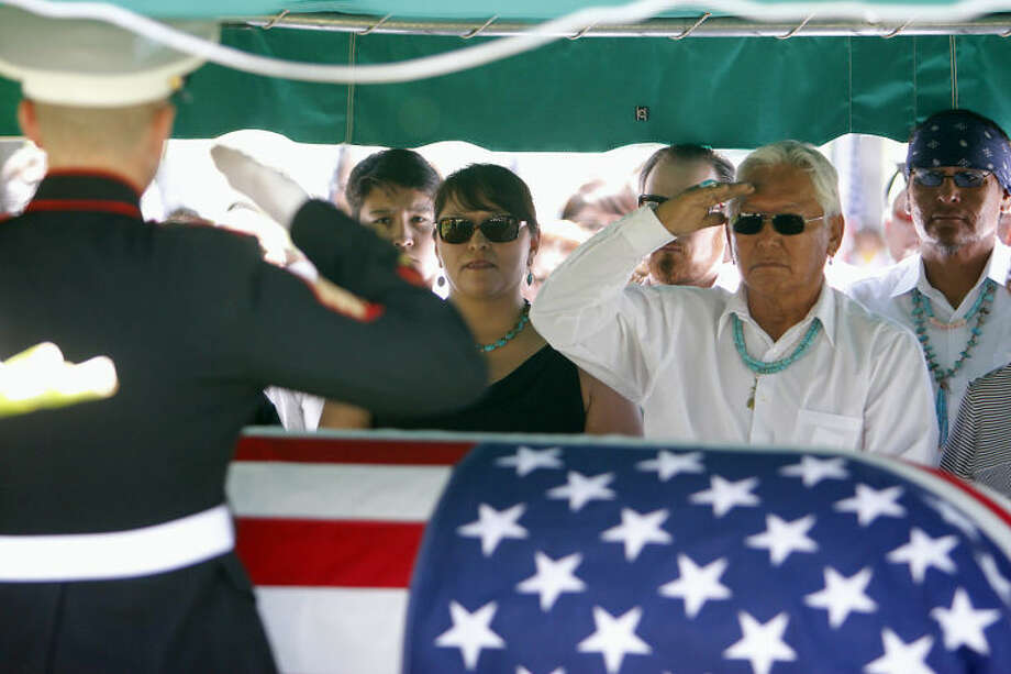 Michael Nez, son of Chester Nez, salutes his father's casket at his father's funeral at the Santa Fe National Cemetery, Tuesday, June 10, 2014, in Sante Fe, N.M. Nez, the last of the 29 Navajos who developed a code that stumped the Japanese during World War II, died Wednesday morning, June 4, 2014. He was 93. (AP Photo/The Santa Fe New Mexican, Luis Sanchez Saturno)