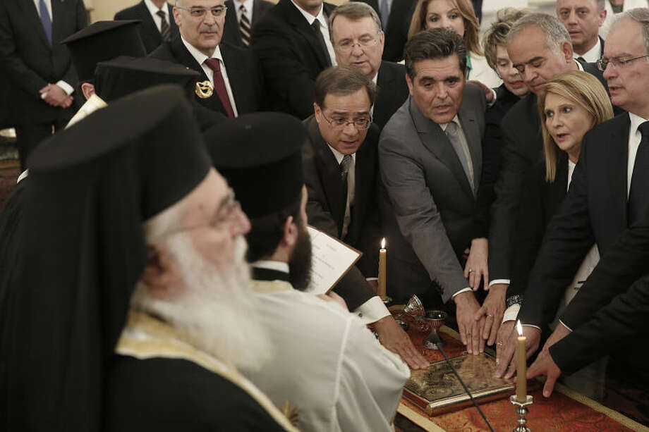 Greece's new Cabinet ministers take the oath of office during a ceremony officiated by Greece's Orthodox Archbishop Ieronimos, at the Presidential palace in Athens, on Tuesday, June 10, 2014. New ministers in the conservative-led government were sworn in Tuesday following a cabinet reshuffle ordered after Greece's anti-bailout left-wing opposition won European parliament elections last month. New Finance Minister Gikas Hardouvelis, centre left, the 59-year-old economics professor and former banking executive, was sworn in as a new report from the International Monetary Fund praised progress made in the crisis-hit country. (AP Photo/Petros Giannakouris)