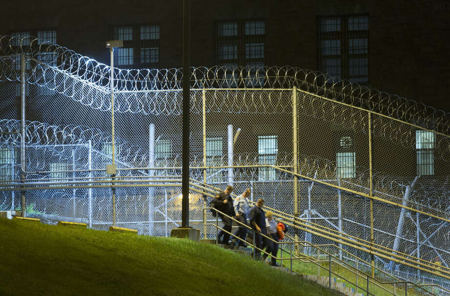 "FILE - In this June 15, 2015, file photo, corrections officers walk next to a fence covered in razor wire as they leave work at Clinton Correctional Facility in Dannemora, N.Y. The June 6 escape by David Sweat and Richard Matt spotlighted apparent security lapses in a prison where a complex escape plan may have been rehearsed for weeks and the breakout went undetected for as long as six hours. But it also bared a culture of surprising liberties and personal relationships in a maximum-security prison where two convicted murderers--one with a history of escaping--were in privileged ""honor"" housing. A guard acknowledged giving one of them tools and access to an off-limits area in exchange for not only prison intel, but also paintings. And an instructor stands accused of helping the two escape after hatching a plot to kill her husband. (AP Photo/Mark Lennihan, File)"