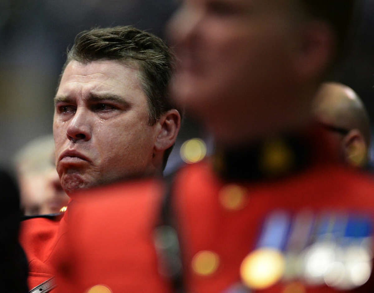 An RCMP gets emotional at the RCMP regimental funeral on Tuesday, June 10, 2014 for the three RCMP officers at the Moncton Coliseum on Tuesday, June 10, 2014, in Moncton, New Brunswick, Canada. Thousands of police officers from across Canada attended the funeral for Fabrice Gevaudan, Douglas Larche and Dave Ross, the three Mounties killed by a gunman on June 4, 2014. (AP Photo/The Canadian Press, Sean Kilpatrick)