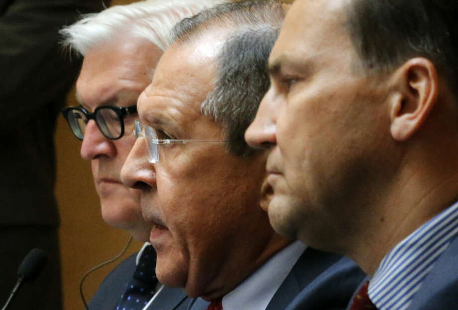 From left, Foreign Ministers, Frank-Walter Steinmeier of Germany, Sergey Lavrov of Russia, and Radoslaw Sikorski of Poland meet with the media after talks on the crisis in Ukraine, in St. Petersburg, Russia, Tuesday, June 10, 2014. (AP Photo/Dmitry Lovetsky)