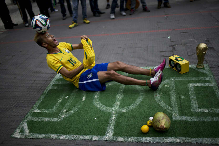 A street performer dressed as a Brazilian national soccer team player, balances a ball on his head during his presentation in downtown Sao Paulo, Brazil, Tuesday, June 10, 2014. The 2014 World Cup is set to begin Thursday, with Brazil and Croatia competing in the opening match in Sao Paulo. (AP Photo/Rodrigo Abd)