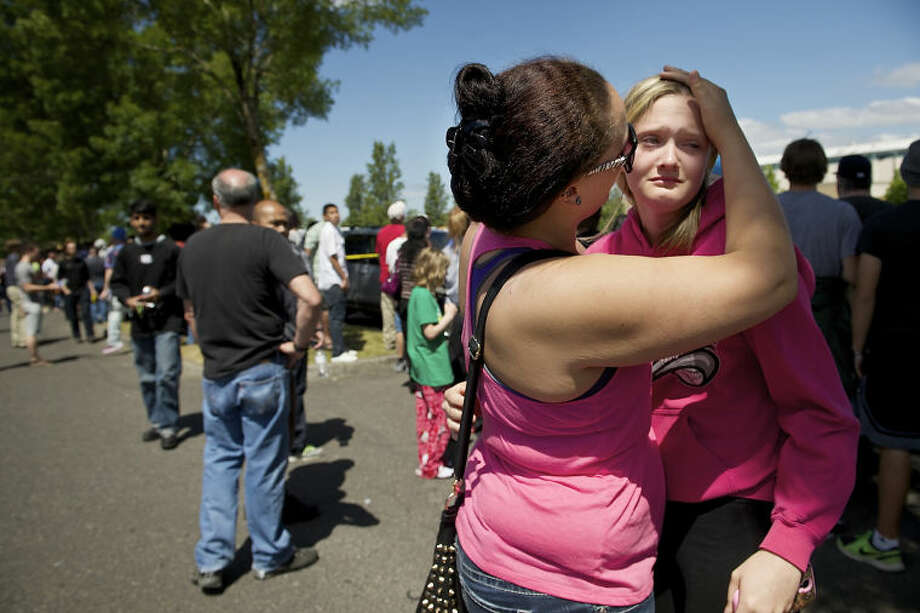 Briannah Wilson, 21, left, comforts her sister, Trisha Wilson, right, 15, as students are reunited with family at a shopping center parking lot in Wood Village, Ore., after a shooting at Reynolds High School Tuesday, June 10, 2014, in nearby Troutdale. A gunman killed a student at the high school east of Portland Tuesday and the shooter is also dead, police said. (AP Photo/Troy Wayrynen)