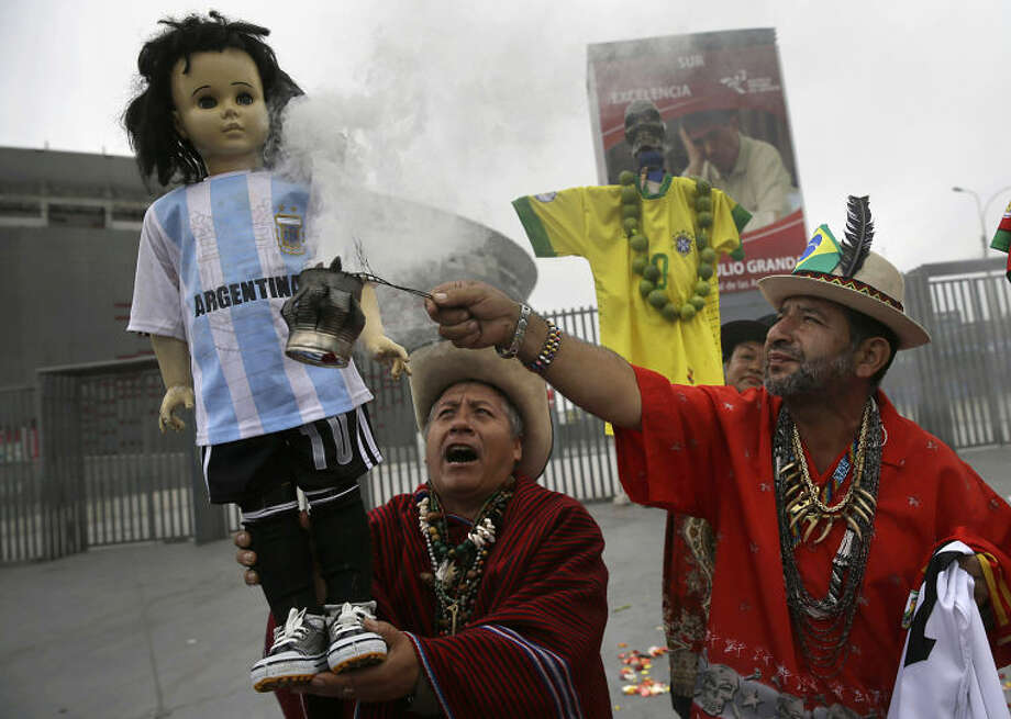 Peruvian shamans perform a good luck ritual using a doll representing Argentina's soccer player Lionel Messi outside the National Stadium in Lima, Peru, Tuesday, June 10, 2014. Soccer fans around the world are gearing up to watch the World Cup soccer tournament that kicks off Thursday in Brazil. (AP Photo/Martin Mejia)