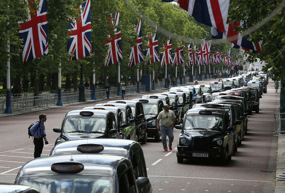 Traditional London black cabs line up along The Mall as taxi drivers stop their black cabs, blocking the street to protest over new technology they say endangers passengers, in London, Wednesday, June 11, 2014. The strike action by taxi drivers hit many European cities, Wednesday, sparked by fears about the growing upheaval in the travel and transport industry, largely due to digital technologies. (AP Photo/Sang Tan)