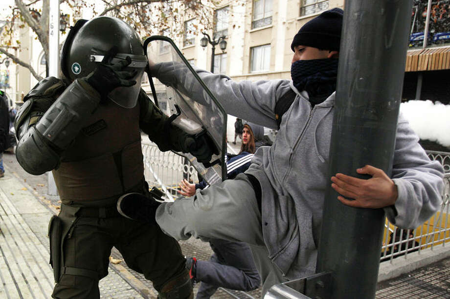 A protester kicks a policeman during a student demonstration in Santiago, Chile, Tuesday, June 10, 2014. Tens of thousands of students protested in Chile demanding education reform since President Michelle Bachelet took power on promises of deep changes. (AP Photo / Luis Hidalgo)