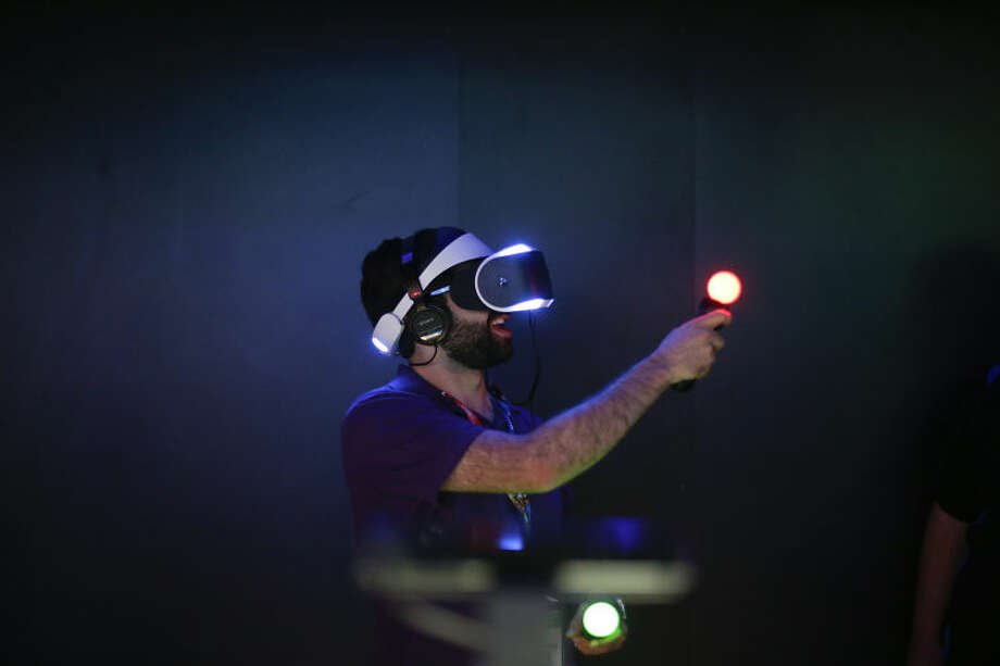 Jordan Saleh plays a video game with Sony's Project Morpheus virtual reality headset at the Electronic Entertainment Expo on Tuesday, June 10, 2014, in Los Angeles. (AP Photo/Jae C. Hong)