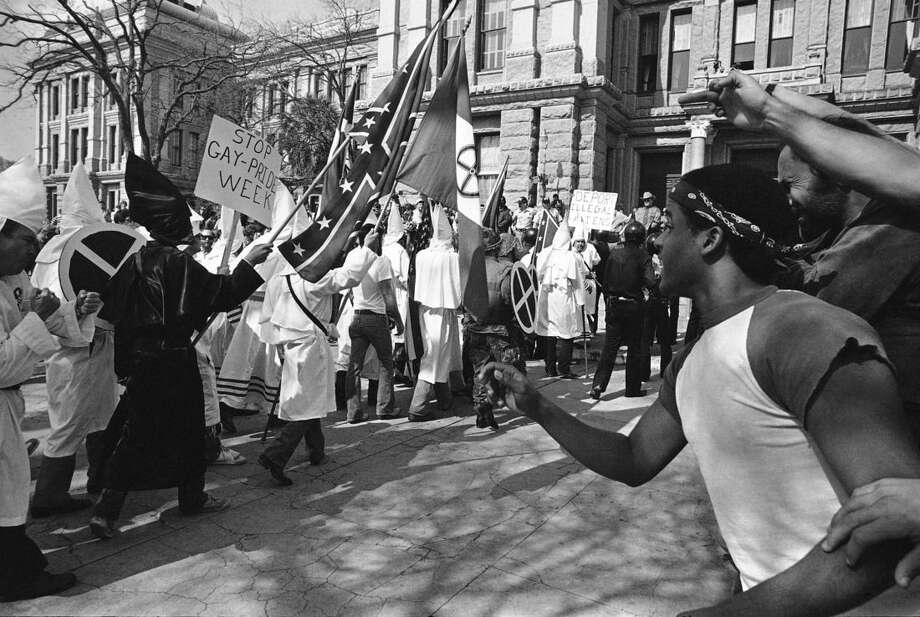 FILE - In this Saturday, Feb. 19, 1983 file photo, anti-Klan demonstrators, right, heckle dozens of members of the Ku Klux Klan at the Texas Capitol in Austin following a short parade nearby. Four hours, several anti-Klan groups staged a parade of their own. (AP Photo/Ted Powers)