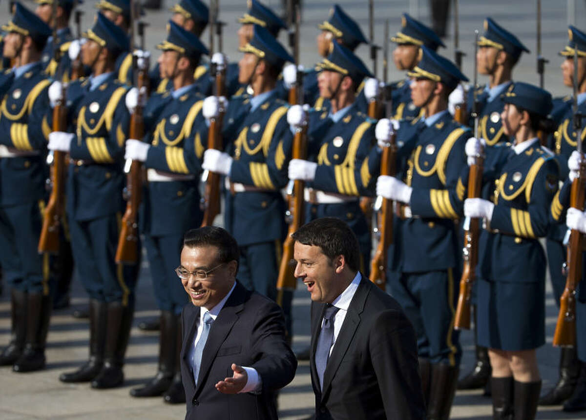 Italian Prime Minister Matteo Renzi, right, chats with his Chinese counterpart Li Keqiang after inspecting a guard of honor during a welcome ceremony outside the Great Hall of the People in Beijing, China Wednesday, June 11, 2014. (AP Photo/Andy Wong)