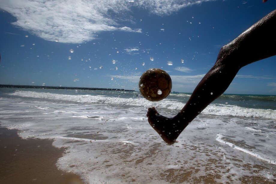 A man kicks a soccer ball on the shores of Beira Mar, in Fortaleza, Brazil, Tuesday, June 10, 2014. Soccer fans around the world are gearing up to watch the World Cup soccer tournament that kicks off in Sao Paulo, Thursday. (AP Photo/Fernando Llano)