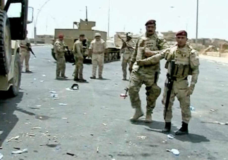 In this Monday, June 9, 2014, image taken from video obtained from the Iraqi military, which has been authenticated based on its contents and other AP reporting, armed Iraqi soldiers take their positions during clashes with militants in the northern city of Mosul, Iraq. Insurgents pressed their efforts Tuesday to seize effective control of Mosul after Iraqi security forces abandoned their posts and militants overran the provincial government headquarters and other key buildings, dealing a serious blow to Baghdad's attempts to tame a widening insurgency. (AP Photo/Iraqi Military via AP video)