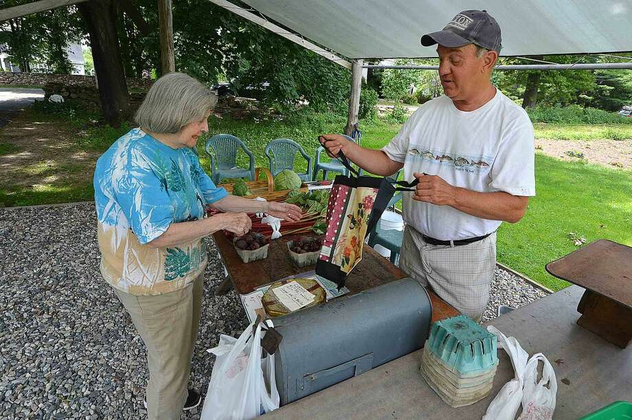 Hour Photo/Alex von Kleydorff Don Offinger helps a customer by giving her a reuseable bag to hold her purchases at Offingers Farm