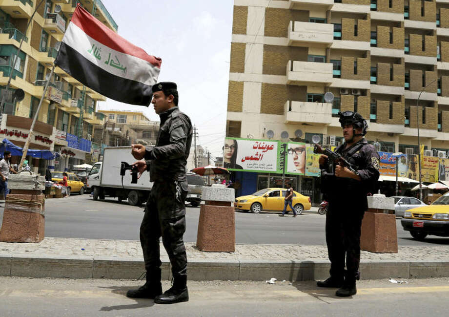 Iraqi federal policemen stand guard at a checkpoint in Baghdad, Iraq, Wednesday, June. 11, 2014. The Iraqi government has tightened its security measures after a stunning assault that exposed Iraq's eroding central authority, al-Qaida-inspired militants overran much of Mosul on Tuesday, seizing government buildings, pushing out security forces and capturing military vehicles as thousands of residents fled the Iraqi second-largest city. (AP Photo/ Karim Kadim)