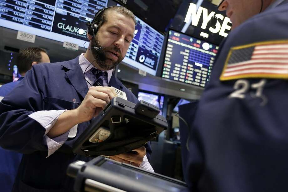 Trader Greg Mulligan works on the floor of the New York Stock Exchange, Monday, June 29, 2015. Stocks are falling in early trading in the U.S., but not as much as in Europe as Greece's debt woes deepen. (AP Photo/Richard Drew)