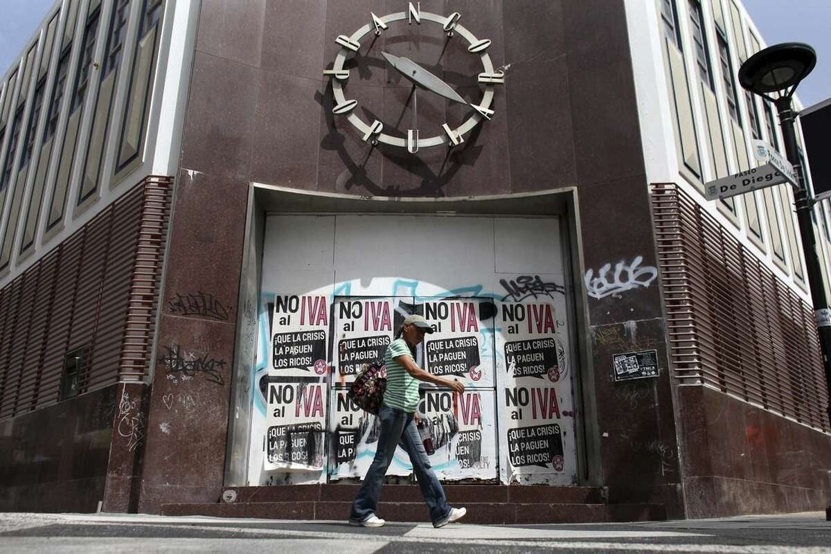 A woman walks in front of a closed down bank in the neighborhood of Rio Piedras in San Juan, Puerto Rico, Monday, June 29, 2015. The bills on the closed bank doors read in Spanish