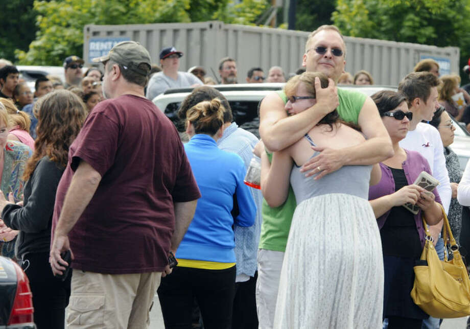 A family embraces as students arrived at the Fred Meyer grocery store parking lot in Wood Village, Ore., after a shooting at Reynolds High School Tuesday, June 10, 2014, in nearby Troutdale. A gunman killed a student at the high school east of Portland Tuesday and the shooter is also dead, police said. (AP Photo/Greg Wahl-Stephens)