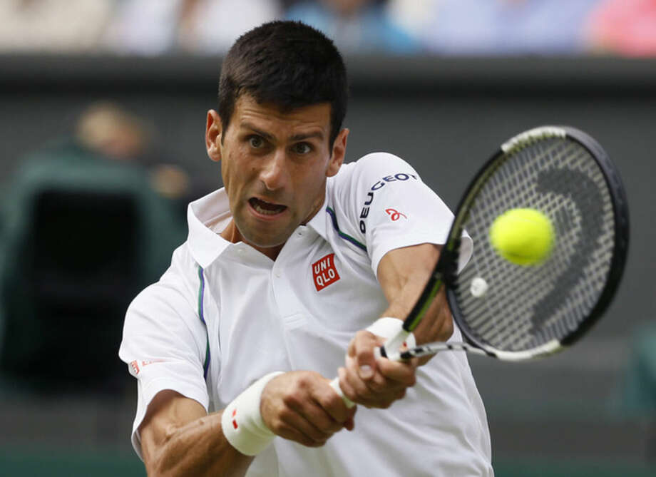 Novak Djokovic of Serbia makes a return to Bernard Tomic of Australia during their singles match at the All England Lawn Tennis Championships in Wimbledon, London, Friday July 3, 2015. (AP Photo/Kirsty Wigglesworth)