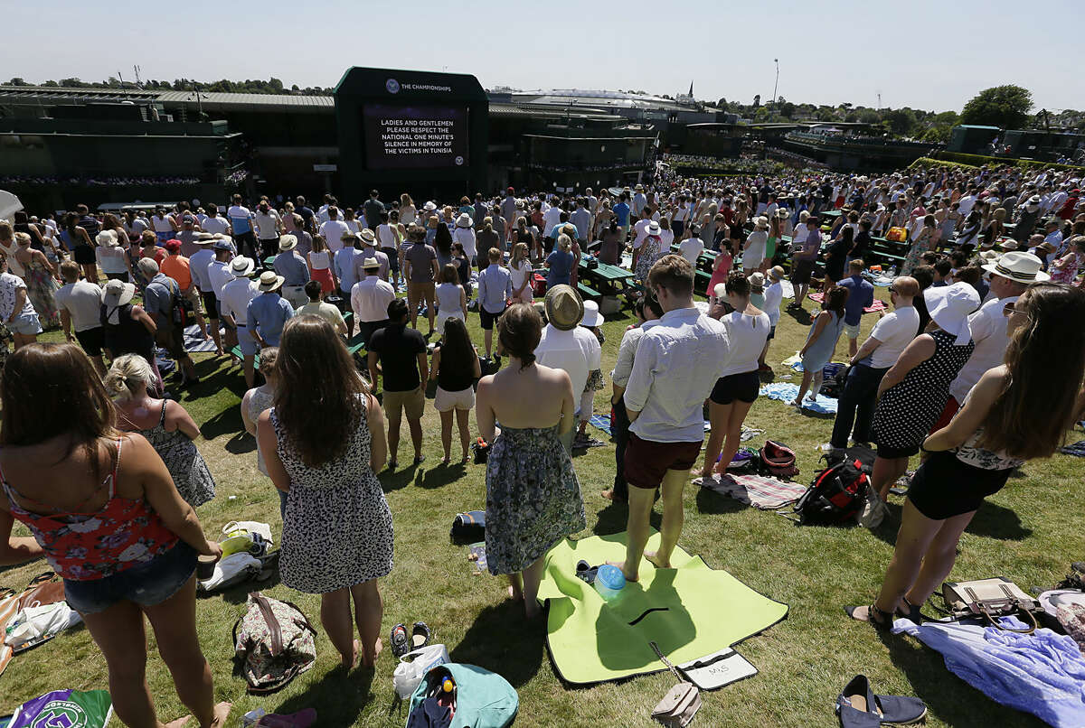 People observe a minute silence for the victims of the shooting in Tunisia last week, at the All England Lawn Tennis Championships in Wimbledon, London, Friday July 3, 2015. Fans and staff at Wimbledon observed a minute's silence for the victims of last Friday's attack in Tunisia, in which 30 Britons were killed in a shooting rampage at a beach resort in Sousse. The start of play at Wimbledon was delayed so the tournament could join in the national minute's silence. (AP Photo/Tim Ireland)