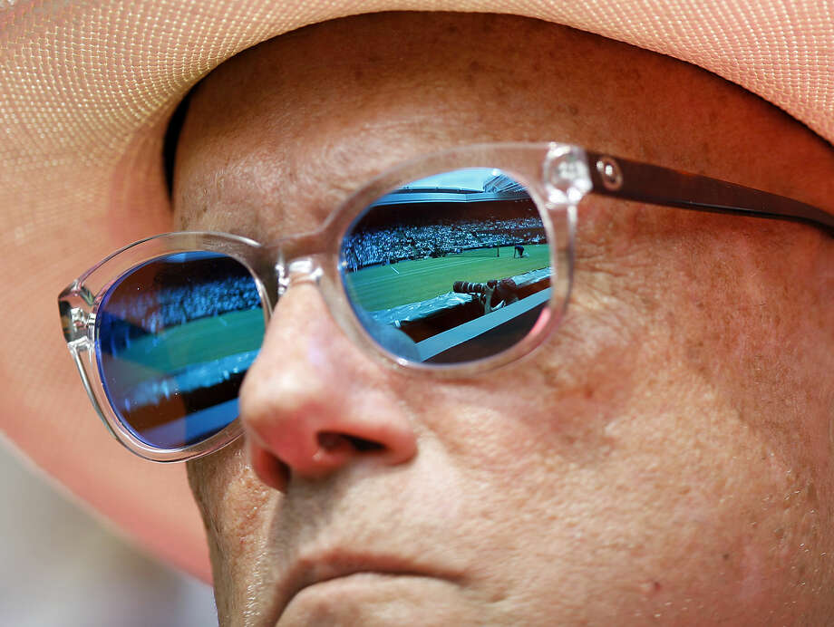 The sunglasses of a spectator reflects the Centre Court at the All England Lawn Tennis Championships in Wimbledon, London, Thursday July 2, 2015. (AP Photo/Pavel Golovkin)