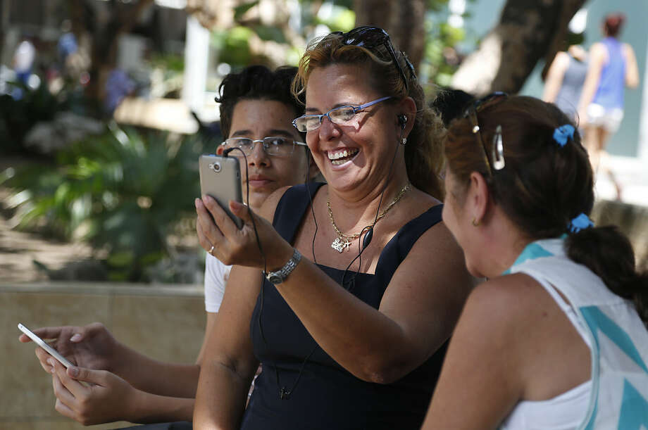 Flanked by her nephew Nelson Suarez, left, and friend Ana Maria Beltran, Laura Martinez communicates with her son in Canada using the first public Wi-Fi hotspot in Havana, Cuba, Thursday, July 2, 2015. Cuban authorities have launched public Wi-Fi hotspots along a main avenue that is the heart of the capital's cultural and social life. Its the first step in government promises to gradually roll out such connectivity options on an island that the internet revolution has largely passed by. (AP Photo/Desmond Boylan)