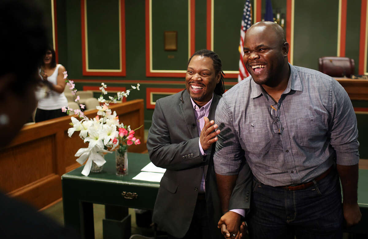 Michael Robinson, left, and Earl Benjamin, partners for almost 14 years, exchange vows before Judge Paula Brown in a ceremony at Orleans Parish Civil District Court on Monday, June 29, 2015, in New Orleans. Court clerks across the state of Louisiana received the go-ahead to issue same-sex marriage licenses Monday. (Kathleen Flynn/NOLA.com The Times-Picayune via AP, POOL)