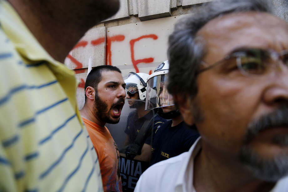 "A member of the Communist-affiliated PAME labor union shouts slogans at the police during an anti-austerity protest calling to ""Vote NO"" outside of the in central Athens, on Friday, July 3, 2015. Greece braced for more chaos on the streets outside its mostly shuttered banks Thursday, as Athens and its creditors halted talks on resolving the country's deepening financial crisis until a referendum this weekend. (AP Photo/Petros Karadjias)"