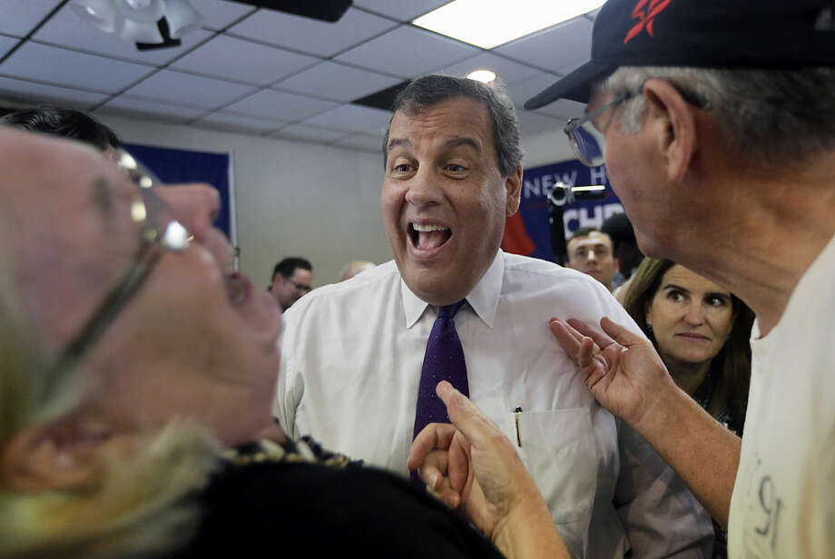 Republican presidential candidate, New Jersey Gov. Chris Christie laughs with potential voters as his wife Mary Pat watches at right, after a campaign town hall meeting, Thursday, July 2, 2015, in Rochester, N.H. (AP Photo/Elise Amendola)