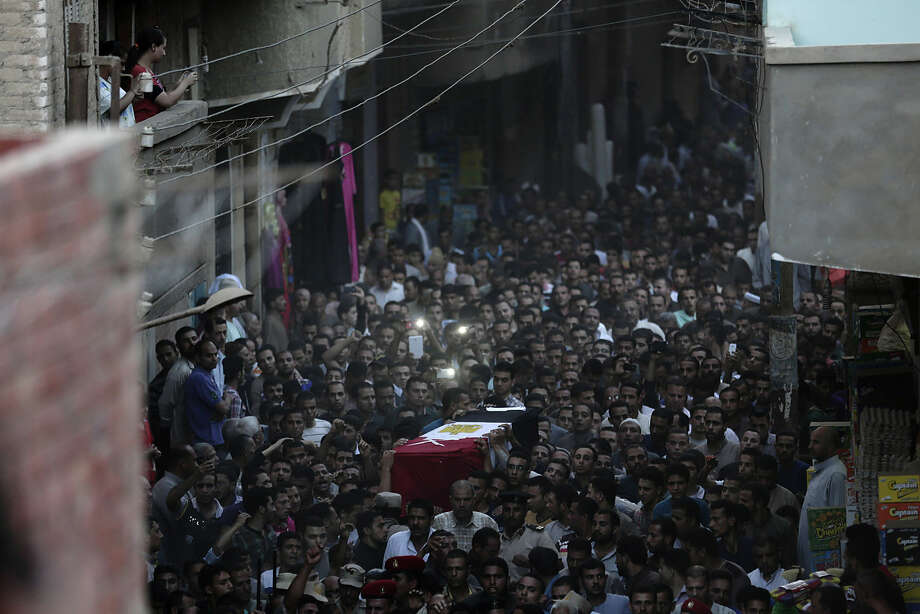 Egyptians carry the coffin of 1st Lt. Mohammed Adel Abdel Azeem, killed in Wednesday's attack by Islamic militants in the Sinai, during the funeral procession at his home village Tant Al Jazeera in Qalubiyah, north of Cairo, Egypt, Thursday, July 2, 2015. Islamic State-linked militants launched an unprecedented wave of attacks in northern Sinai the previous day, setting off the fiercest fighting the peninsula has seen in decades and undermining government efforts to stem the insurgency. (AP Photo/Hassan Ammar)