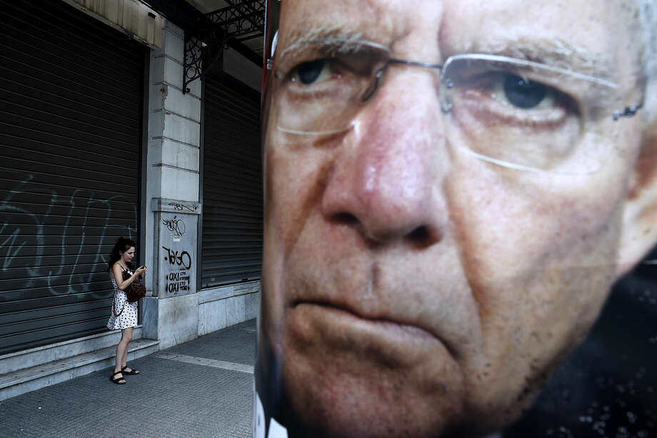 A woman uses her cell phone next to a poster depicting German Finance Minister Wolfgang Schaeuble placed by supporters of the No vote to the upcoming referendum in the northern Greek port city of Thessaloniki, Friday, July 3, 2015. Greeks will vote Sunday on whether to accept a proposal that creditors had made of specific reforms in exchange for loans. European Union institutions are framing it as a vote for or against the euro. (AP Photo/Giannis Papanikos)