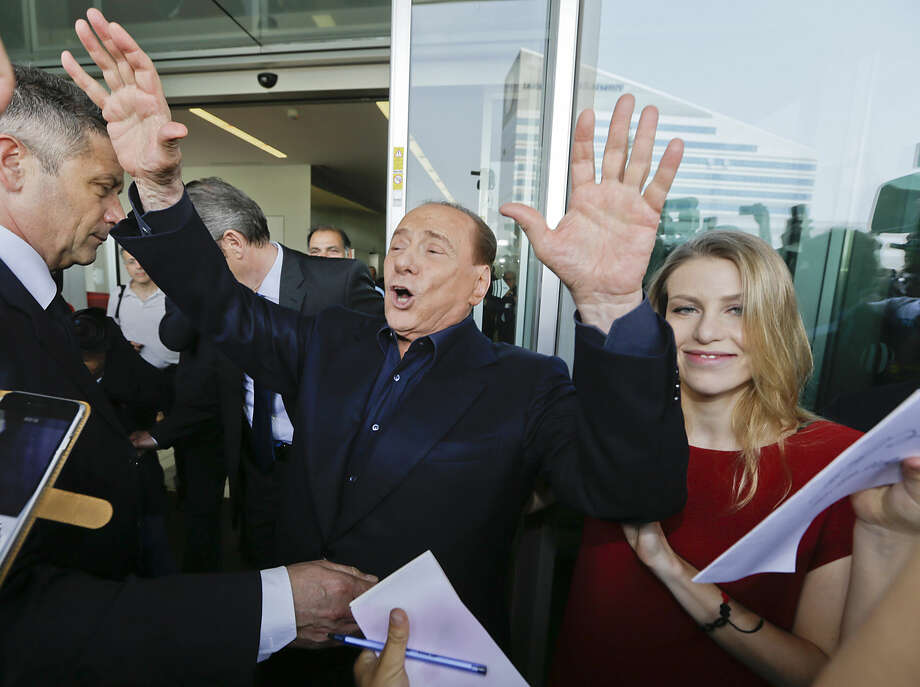AC Milan president Silvio Berlusconi waves to supporters flanked by his daughter Barbara, outside the Milanese soccer club's headquarters, in Milan, Italy, Friday, July 3, 2015. Berlusconi has demanded new coach Sinisa Mihajlovic lead the club back into the Champions League. (AP Photo/Luca Bruno)