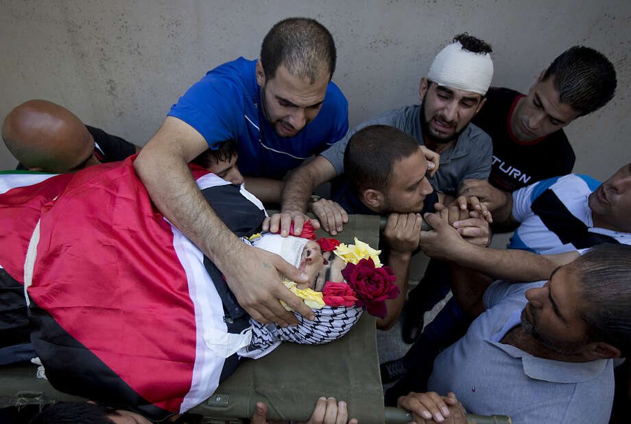 Palestinians surround the body of Mohammed Kasbah, 17, who was killed in the clashes with Israeli forces, during his funeral in the Qalandia refugee camp near the West Bank city of Ramallah, Friday, July 3, 2015. Israel's military says troops opened fire and killed the Palestinian who was among a group that threw large rocks at their vehicle. (AP Photo/Majdi Mohammed)