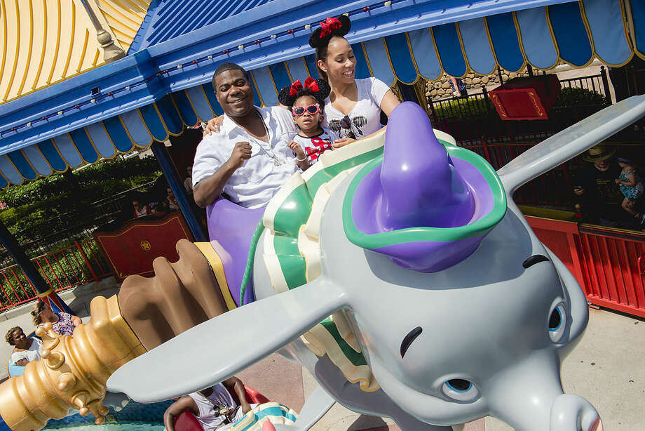 In this image released by Disney, actor-comedian Tracy Morgan, left, his fiancée Megan Wollover, right, and daughter Maven Morgan, 2, ride on Dumbo the Flying Elephant at Magic Kingdom theme park in Lake Buena Visa, Fla. Tracy Morgan, who was seriously injured June 7, 2014 in a car crash on the New Jersey Turnpike, was at the park to celebrate Maven's birthday. (Chloe Rice, photographer)