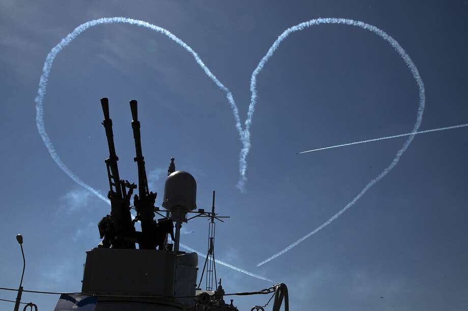"""L-39 jets of the """"Russ"""" aerobatic team create by smoke a heart pierced by an arrow during an air show at the International Maritime Defence show in St.Petersburg, Russia, Thursday, July 2, 2015. (AP Photo/Dmitry Lovetsky)"""