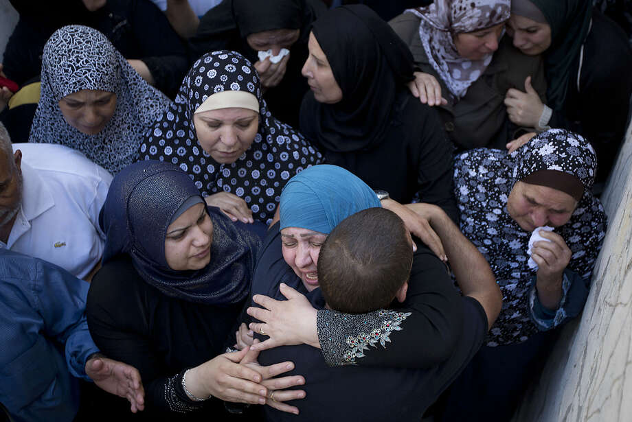 Relatives mourn for Mohammed Kasbah, 17, who was killed by Israeli forces, during his funeral in the Qalandia refugee camp near the West Bank city of Ramallah, Friday, July 3, 2015. Israel's military says troops opened fire and killed the Palestinian who was among a group that threw large rocks at their vehicle. (AP Photo/Majdi Mohammed)