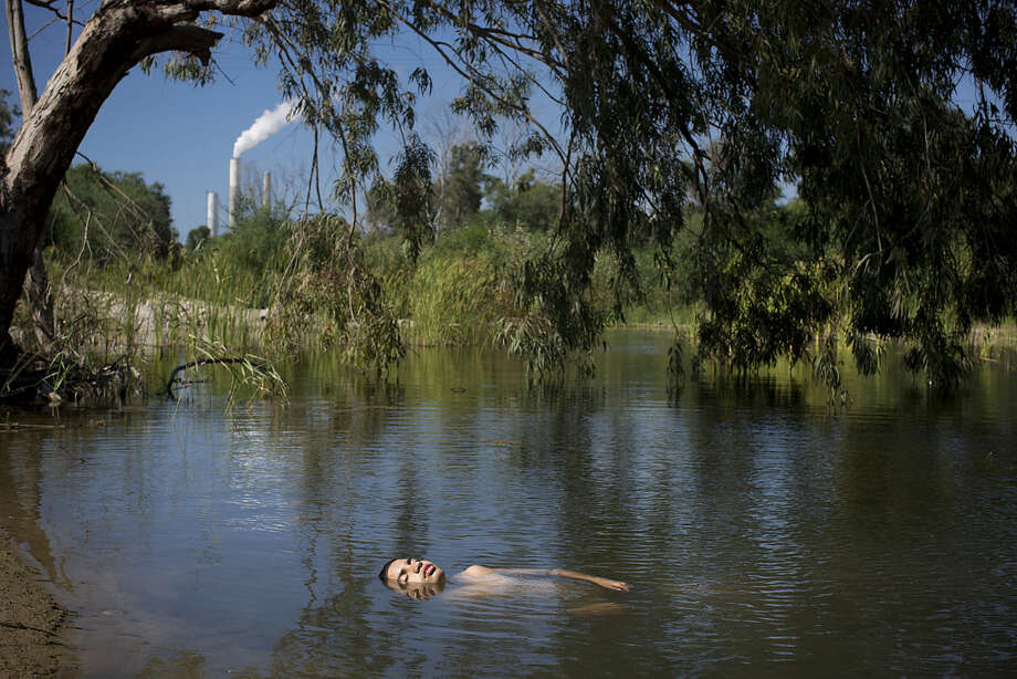 In this Sunday, June 21, 2015 photo, an Israeli youth bathes in a stream next to kibbutz Zikim, on the Israel-Gaza border. A year after the Gaza war, the community in southern Israel, long battered by rockets from the Hamas-run territory next door, has slowly recovered and is even seeing a quiet boom. (AP Photo/Oded Balilty)