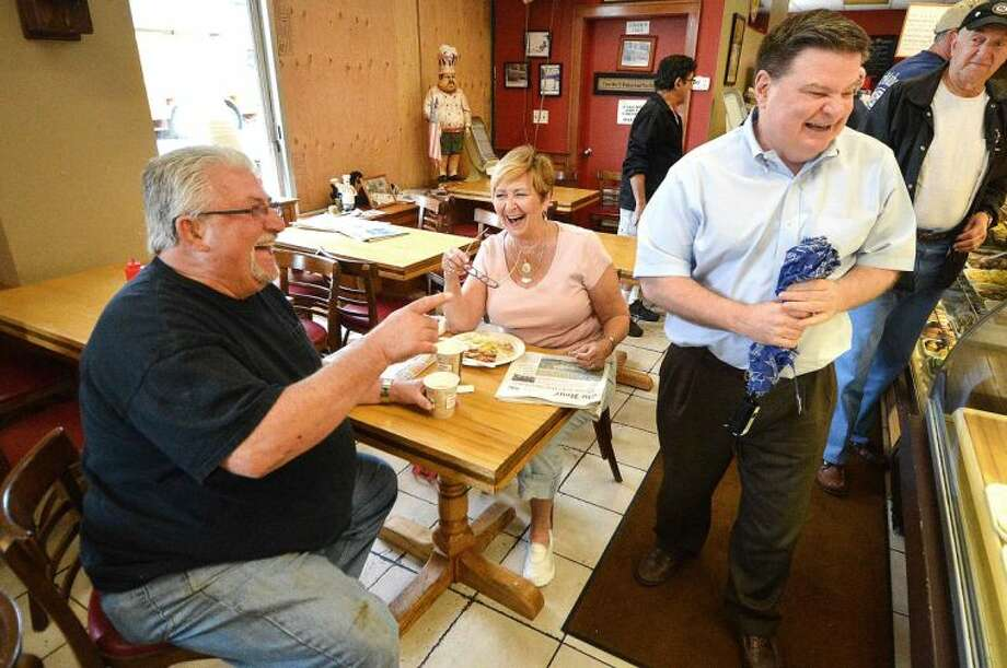 Hour Photo/Alex von Kleydorff Dominic and Judi Muro share a lighter moment with a customer at the bakery on Main St. that sustained damage from a transformer explosion yesterday but they were able to open for regular hours Wednesday