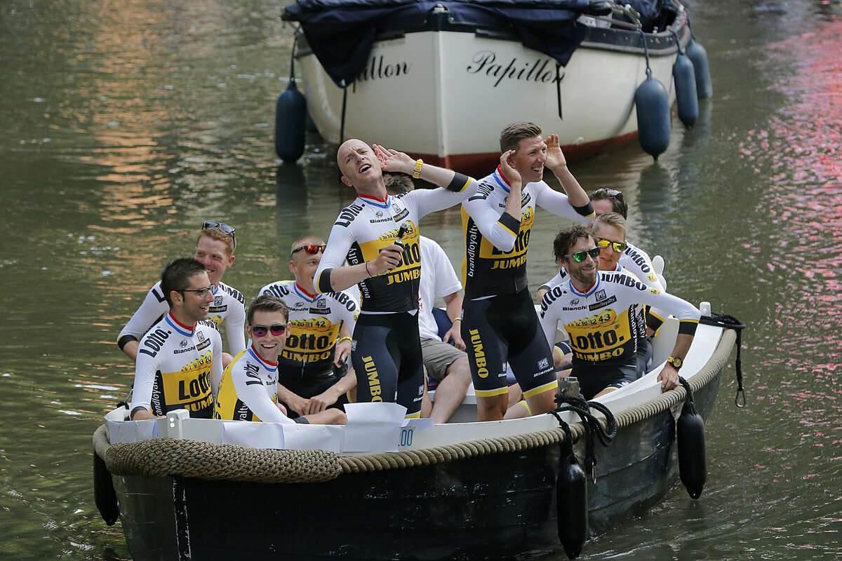 Team Lotto Jumbo with Jos van Emden, center standing, and Belgium's Sep Vanmarcke, center right standing, urge the crowd to cheer louder as they arrive for the team presentation in Utrecht, Netherlands, Thursday, July 2, 2015, two days ahead of the start of the Tour de France cycling race. (AP Photo/Christophe Ena)