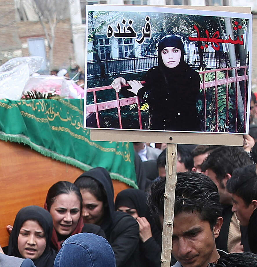 "In this Tuesday, March 24, 2015 photo, Afghan women carry the coffin of Farkhunda, seen on the poster, who was beaten to death by a mob after being falsely accused of burning a Quran, during her funeral in downtown Kabul, Afghanistan. An Afghan court has overturned the death sentences for four men convicted of taking part in the mob killing of Farkhunda outside a Kabul shrine, a judge said Thursday, July 2, 2015. The poster reads, ""martyr Farkhunda."" (AP Photo/Massoud Hossaini)"