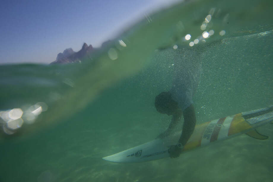 In this June 10, 2015 photo, Magno Neves dives with his board at Arpoador beach in Rio de Janeiro, Brazil. Neves, a 23-year-old from the Cantagalo slum, surfs nearly every day at the nearby Arpoador beach. (AP Photo/Felipe Dana)